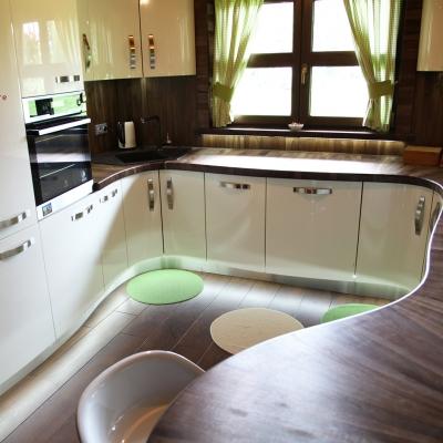 Orechová kuchyňa v kombinácii s vysokým leskom s oblými dvierkami s podsvietením